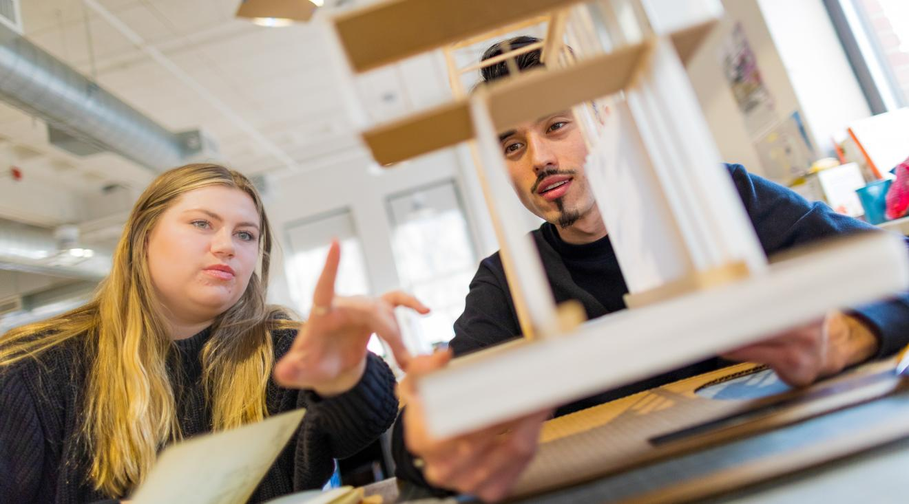 A female and male student examine an architectural model.