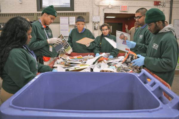 A diverse group of students sorting recycling