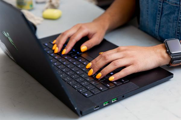 A woman's hands with yellow nail polish typing on a laptop.