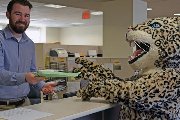 Leopard mascot accepting paper from man behind a counter.