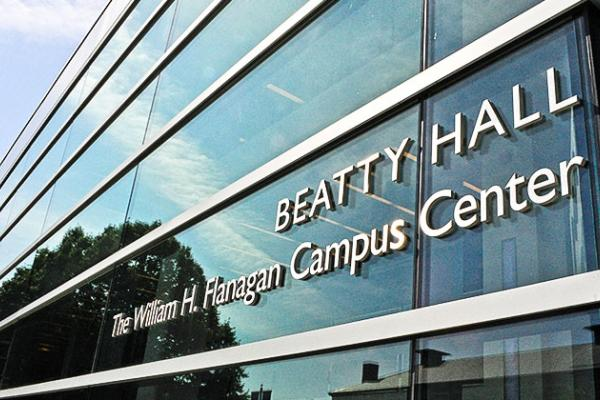 "The sign on the glass outside of Beatty Hall that reads ""Beatty Hall. The William H. Flanagan Campus Center"""