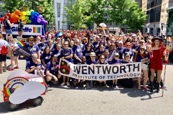 large group of people holding up a wentworth banner