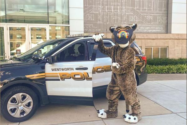 The leopard mascot poses in front of a public safety vehicle.