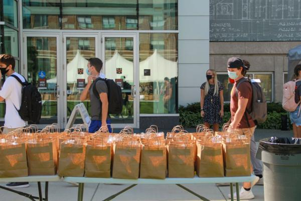 A few students file past the paper bag lunches set out for them on a table in the Quad.