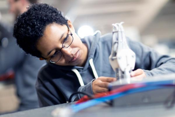 A female student examines a mechanical part.