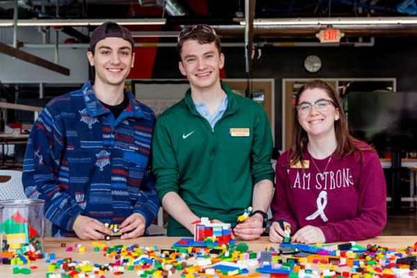 Two male students and one female student smile at the camera in front of a table of legos.