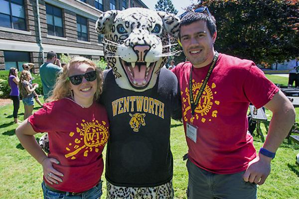 A female and male student pose on the Quad with the leopard mascot.