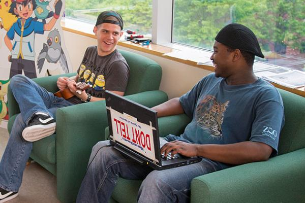Two male students sitting next to each other and chatting. The student on the left plays the ukulele while the student on the right works on his laptop