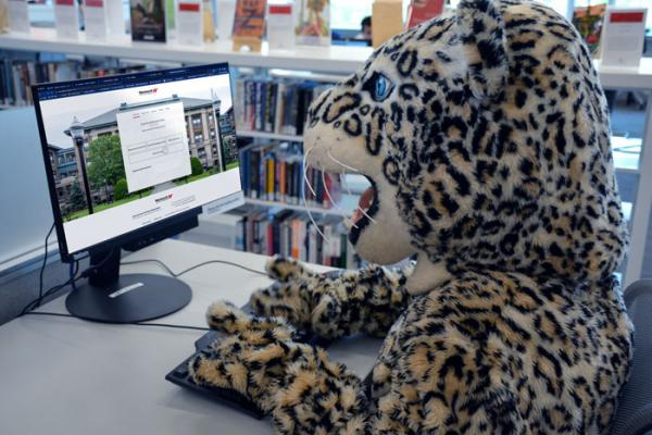 The leopard mascot sits in front of computer looking at the Wentworth donation page.