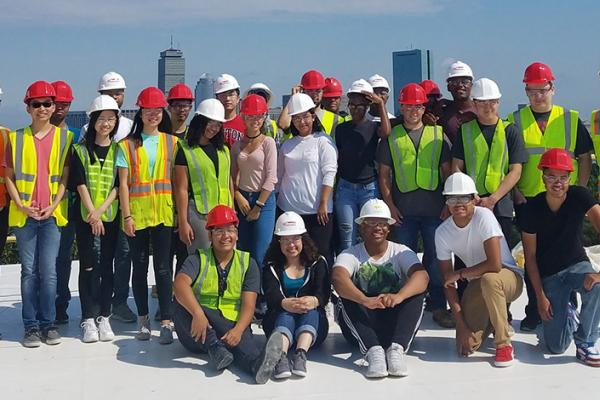 A group of construction management students in front of Boston's skyline.