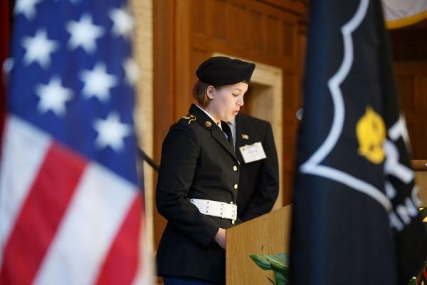 woman in military uniform speaking next to american flag