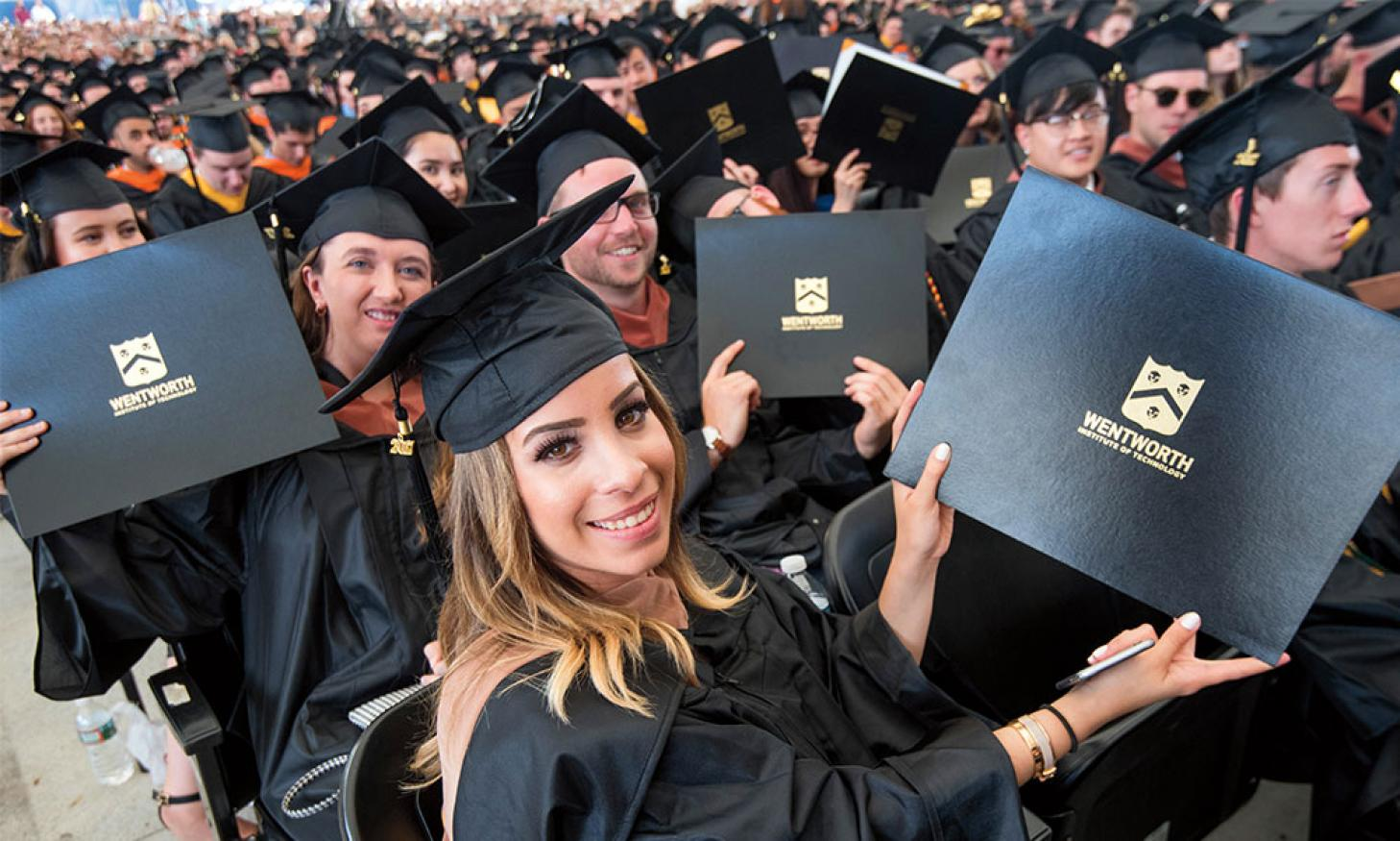 A picture of students in cap and gown holding up their diplomas