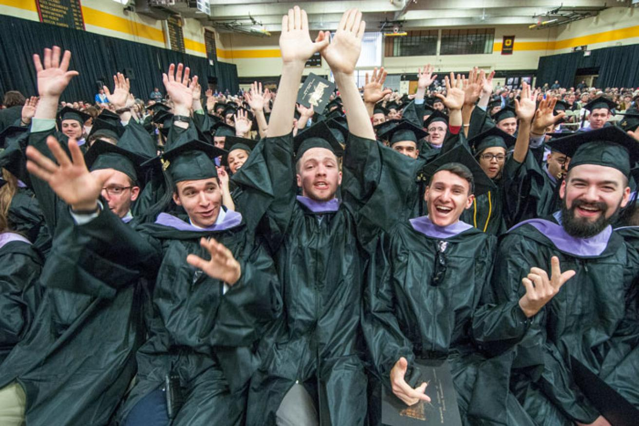 A group of students celebrate in their commencement cap and gown