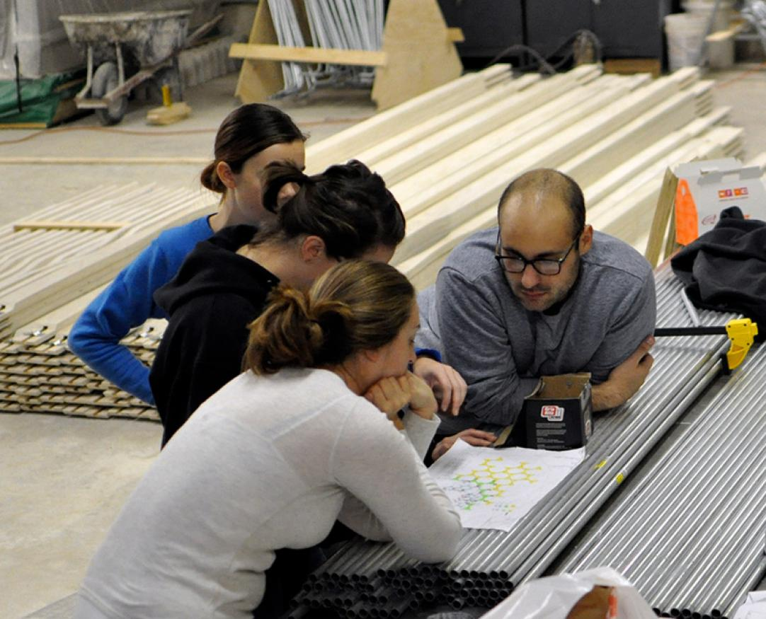 A group of students pour over a blueprint in a construction lab.