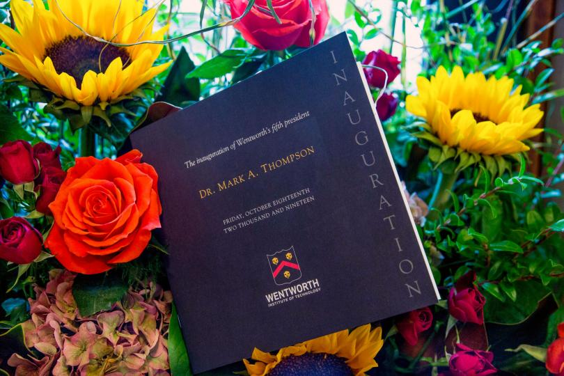 A photo of the inauguration program placed in a flower arrangement