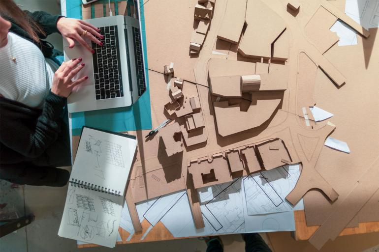 A woman's hands are in view as she works on her laptop surrounded by a cardboard architectural model.