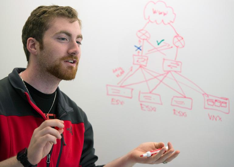 Male student explains diagram written on whiteboard.