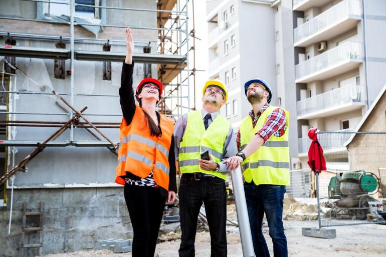 woman and two men on job site looking up