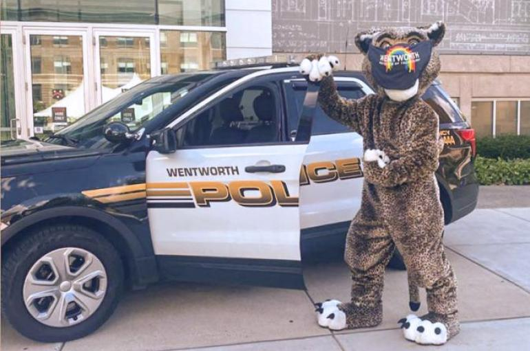 Leopard mascot wearing a mask in front of a Wentworth police car.