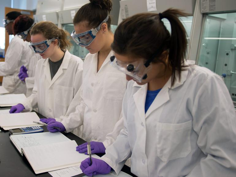 Women in lab gear working on class notes.