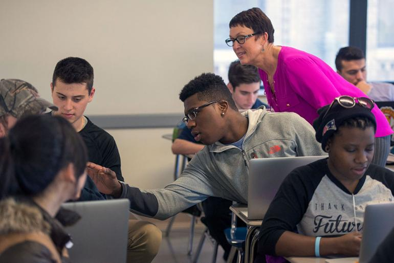 Cindy Stevens works with students in classroom.